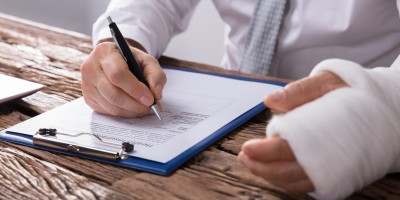 image of man with cast signing medical paperwork