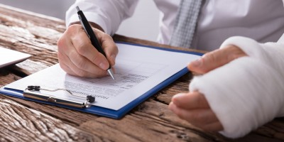 man with cast signing medical paperwork